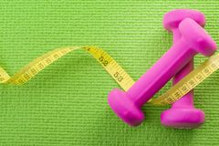 Healthy lifestyle, fitness and weight control concept with a closeup pink on a pair dumbbells with measuring tape wrapped around. Them on a green yoga mat stock photo