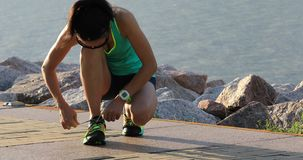 Healthy lifestyle fitness woman runner tying shoelace before running on sunny seaside. Fitness woman runner tying shoelace before running on sunny seaside stock video