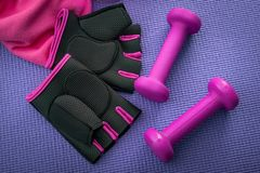 Healthy lifestyle, fitness and yoga concept with girly workout equipment like a pink pair of gym gloves, two dumbbells or weights. And a pink towel on a purple stock photo