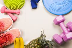 Healthy lifestyle, food, sport or athlete`s equipment on bright. Background. rnsneakers, weights, fruits, vegetables,Flat lay. Top view with copy space..Fitnes Stock Images
