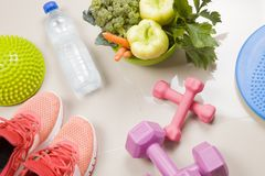 Healthy lifestyle, food, sport or athlete`s equipment on bright. Background. rnsneakers, weights, fruits, vegetables,Flat lay. Top view with copy space..Fitnes Stock Photography