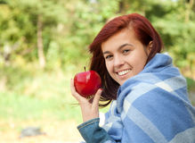 Healthy lifestyle - girl with red apple, outdoors Royalty Free Stock Image
