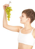 Healthy lifestyle - girl in sport bra with grapes Royalty Free Stock Images