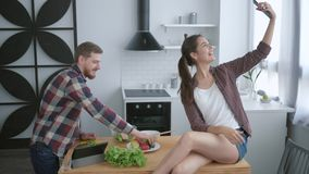Healthy lifestyle, happy family makes selfie photo on mobile phone while preparing healthy food from fresh vegetables. And greens on kitchen table stock footage