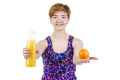 Healthy lifestyle, healthy eating. Young girl with a bottle of orange juice and orange, smiling, on a white isolated background. H stock photography