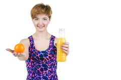Healthy lifestyle, healthy eating. Young girl with a bottle of orange juice and orange, smiling, on a white isolated background. H royalty free stock images