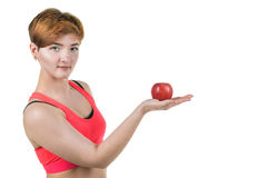 Healthy lifestyle, healthy eating. Young girl holds a red apple on her hand, on a white isolated background. Horizontal frame royalty free stock photo