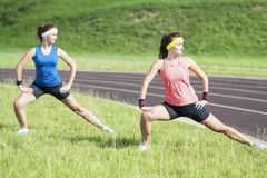 Healthy Lifestyle Ideas and Concepts. Two Young Caucasian Girlfriends in Athletic Sportswear Having Trunk Bending Exercises Stock Photography