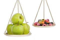 Healthy lifestyle metaphor. Balance with sweets and apples, metaphor for healthy living, isolated on white background Royalty Free Stock Images