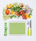 Healthy lifestyle and modern dieting concept. Various fresh salad vegetables with cutlery and measuring tape around PC tablet . C Stock Photo