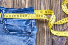 Healthy lifestyle and nutrition concept. Blue jeans with a measuring tape instead of a belt. Close up of jeans with a measuring tape around the waist. Top of stock photography
