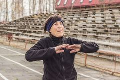 Older woman doing outdoor exercise. Healthy lifestyle in old age. older woman doing outdoor exercise. pensioner doing exercise for hands royalty free stock image