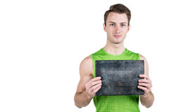 Healthy lifestyle. Portrait of a handsome guy with a blank signboard for writing, in sportswear, isolated on a white background, l Stock Photos