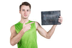 Healthy lifestyle. Portrait of a handsome guy with an empty signboard for writing, wearing sportswear, isolated on white backgroun Royalty Free Stock Image