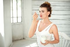 Healthy Lifestyle. Portrait Of Smiling Woman Tasting Fresh Organic Yogurt sitting in white bright room, wearing in white Stock Photos
