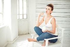 Healthy Lifestyle. Portrait Of Smiling Woman Tasting Fresh Organic Yogurt sitting in white bright room, wearing in white Stock Photo