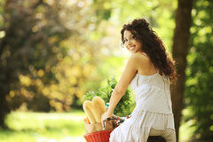 Healthy Lifestyle. Portrait of a smiling young woman riding bicycle with groceries in basket stock images