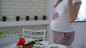 Healthy lifestyle of pregnant female with big tummy is cooking useful delicious food for dinner from fresh vegetables at stock footage