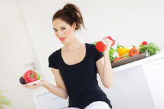 Healthy Lifestyle Propaganda. Young woman sitting with dumbell and veggie plate. Healthy lifestyle concept Stock Images