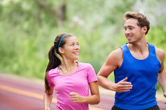 Healthy lifestyle - Running fitness couple jogging. Laughing, talking outside on road in beautiful nature. Multiracial sports couple, Asian women model and men stock photos