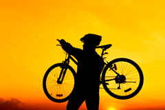 Healthy lifestyle. Silhouette of bicyclist carrying his bicycle Stock Image