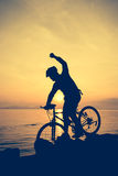 Healthy lifestyle. Silhouette of bicyclist riding the bike at se Stock Image