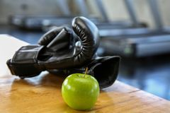Healthy lifestyle sport. Boxing glove, and healthy food on wooden. green apple in the gym or sport club. Healthy lifestyle sport royalty free stock image