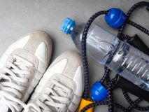 Healthy lifestyle and sport concept. White sneakers, expander and bottle of water on a grey background. Fitness concept royalty free stock image