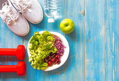 Healthy lifestyle sport equipment fitness, sneakers, green apple, fresh water and healthy food on blue wood background stock image