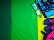 Healthy lifestyle. Sport and healthy nutrition. Top view of sports equipment, running shoes, leggings tshirt, green mat, sports. Water bottle. Flat lay with royalty free stock photos