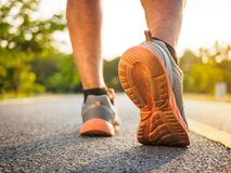 Healthy lifestyle sports man legs running and walking while exercising outdoors during sunrise or sunset. Moving forward to stock images