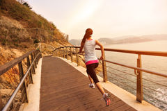 Healthy lifestyle sports woman running. On wooden trail seaside Stock Image