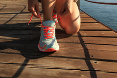 Healthy lifestyle sports woman tying shoelaces. On wooden boardwalk sunrise seaside stock image