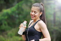 Healthy lifestyle sporty woman with headphone and bottle of wate. Healthy lifestyle fitness sporty woman running early in the morning in forest area, healthy Royalty Free Stock Image