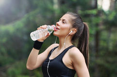 Healthy lifestyle sporty woman with headphone drinking water in stock image