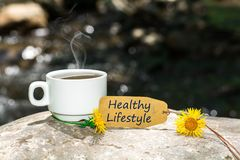 Healthy lifestyle text with coffee cup. Healthy lifestyle text in tag with coffee cup and yellow flower on rock in the river , shine bokeh background royalty free stock photography