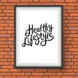 Healthy Lifestyle Texts in Frame Hanging on a Wall. Conceptual Healthy Lifestyle Texts in Black Font Style Inside a White Rectangular Photo Frame Hanging on Royalty Free Stock Photography