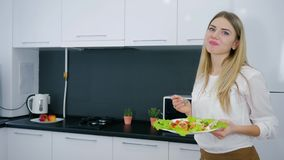 Healthy lifestyle, useful food in hands of attractive girl during lunch at home. In kitchen stock video footage