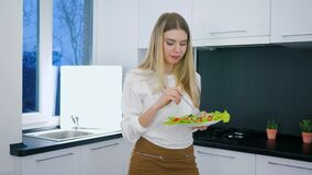 Healthy lifestyle, vegetarian meal of beautiful girl with plate of lettuce in hands during dinner in kitchen. Healthy lifestyle, vegetarian meal of beautiful stock footage