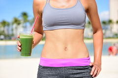 Healthy lifestyle woman drinking green smoothie. Healthy lifestyle fitness woman drinking green vegetable smoothie juice after running exercise.  Close up of Stock Photo