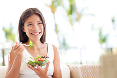 Healthy lifestyle woman eating salad smiling happy. Outdoors on beautiful day. Young female eating healthy food outside in summer dress laughing and relaxing in Stock Photography