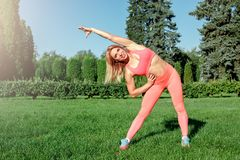 Healthy Lifestyle. Woman practicing yoga outdoors bending to the side cheerful royalty free stock photography