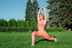 Healthy Lifestyle. Woman practicing yoga outdoors in low lunge pose concentrated. Young woman practicing yoga outdoors at park standing in low lunge pose stock image