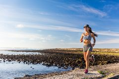 Healthy lifestyle woman runner running outside. On summer nature trail by ocean beach. Happy Asian athlete training cardio and endurance outdoors. Motivation stock photo