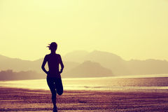 Healthy lifestyle woman running at sunrise beach Stock Photography