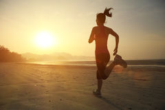 Healthy lifestyle woman running at sunrise beach Stock Image
