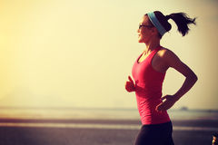 Healthy lifestyle woman running at sunrise beach Royalty Free Stock Photography