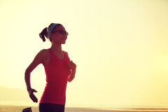 Healthy lifestyle woman running at sunrise beach Royalty Free Stock Image