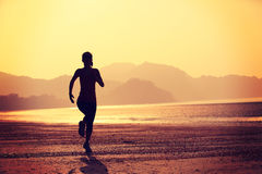 Healthy lifestyle woman running at sunrise beach Royalty Free Stock Photo