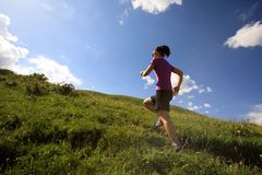 Woman trail runner running on mountain trail Stock Image